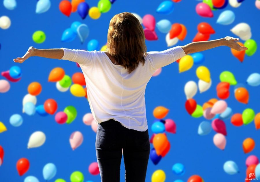 woman with arms out in front of colourful balloons